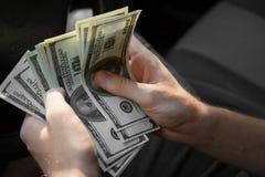 Бизнесмен подсчитывая деньги Укомплектуйте личным составом руки ` s с долларами в автомобиле на запачканной предпосылке Финансова Стоковая Фотография