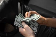 Бизнесмен подсчитывая деньги Укомплектуйте личным составом руки ` s с долларами в автомобиле на запачканной предпосылке Финансова Стоковые Фото