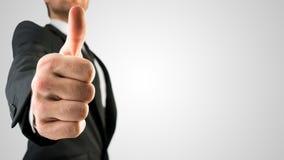 Бизнесмен показывая большие пальцы руки вверх подписывает внутри близко вверх Стоковое Изображение RF