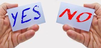 Бизнесмен показывая да в голубом цвете и нет в карточках красного цвета в его руках Стоковая Фотография