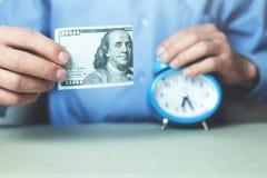Бизнесмен показывая 100 долларов белизна времени дег предпосылки изолированная принципиальной схемой Стоковое Изображение RF