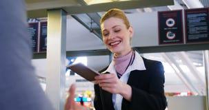 Бизнесмен показывая его посадочный талон на счетчике регистрации акции видеоматериалы