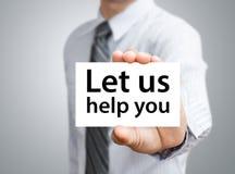 Бизнесмен показывая карточку с позволил нам помочь вам отправить СМС Стоковая Фотография