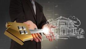 Бизнесмен показывая ключ здания Стоковое фото RF