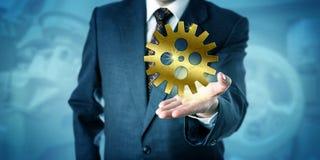 Бизнесмен показывая один золотой Cog катит внутри ладонь стоковые фото