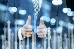Бизнесмен показывая положительный жест с его руками стоя за стрелками идя вверх Концепция доход от стоковое изображение