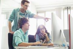 Бизнесмен показывая что-то к коллегам на компьютере в творческом офисе Стоковое фото RF