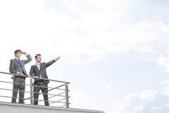 Бизнесмен показывая что-то к сотруднику против облачного неба Стоковые Фотографии RF