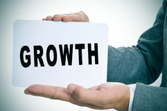 Бизнесмен показывая шильдик с ростом текста Стоковая Фотография
