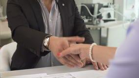 Бизнесмен покупая новую квартиру и тряся руки с женским маклером на офисе сток-видео