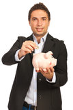 Бизнесмен положил монетку к piggy Стоковые Фото