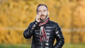 Бизнесмен портрета дружелюбный молодой имея работая диалог используя смартфон на открытом воздухе акции видеоматериалы