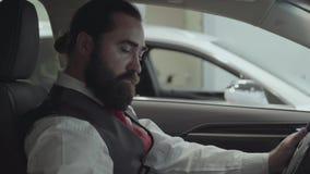 Бизнесмен портрета привлекательный уверенный бородатый сидя в корабле и проверяет заново купил автоматическое от автомобиля акции видеоматериалы