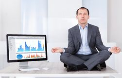 Бизнесмен посредничая компьютером на столе Стоковое фото RF