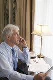 Бизнесмен постаретый серединой на звонке на столе Стоковая Фотография