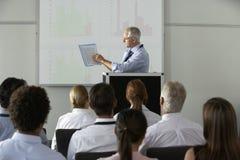 Бизнесмен постаретый серединой поставляя представление на конференции стоковая фотография rf