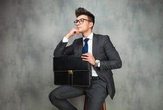Бизнесмен полагаясь его локоть против стены и взглядов прочь стоковые изображения rf