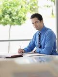 Бизнесмен подготавливая примечания на столе в офисе Стоковые Изображения