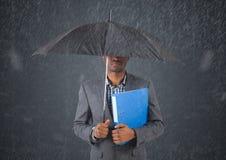 Бизнесмен под зонтиком против в дождя против серой предпосылки Стоковое Изображение RF