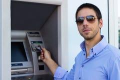 Бизнесмен положил его кредитную карточку на ATM стоковые изображения rf