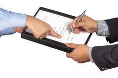 Бизнесмен подписывает контракт указывая руки клиента Стоковая Фотография RF