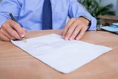 Бизнесмен подписывая контракт в офисе Стоковое Фото