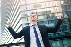 Бизнесмен празднуя поднимать его оружия после хороших новостей стоковые изображения
