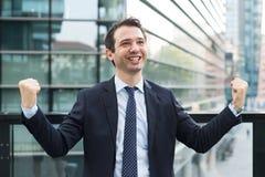Бизнесмен празднуя поднимать его оружия после хороших новостей стоковая фотография
