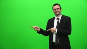 Бизнесмен представляя перед зеленым экраном акции видеоматериалы