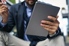 Бизнесмен преследуя над кредитной карточкой и используя iPod стоковые изображения rf