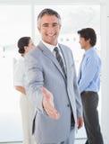 Бизнесмен предлагая трясти руки Стоковые Изображения