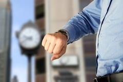 бизнесмен предпосылки проверяя его изолированную белизну вахты времени Стоковая Фотография