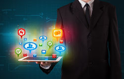 Бизнесмен представляя современную таблетку с цветастыми социальными знаками Стоковые Изображения