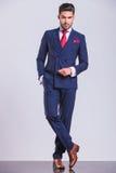 Бизнесмен представляя стоящие ноги пересек с рукой в карманн стоковое изображение rf