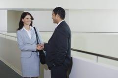 Бизнесмен приветствуя женского коллеги в офисе Стоковая Фотография