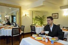 Бизнесмен принимает завтрак в гостинице стоковое фото rf