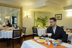 Бизнесмен принимает завтрак в гостинице Стоковое Фото