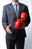 Бизнесмен принимает перчатки бокса для того чтобы предложить рукопожатие на белизне Стоковые Фото