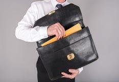 Бизнесмен принимая папку из его портфеля Стоковое Изображение RF