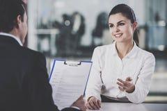 Бизнесмен принимая резюме от женщины в офисе Стоковое Изображение RF