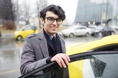 Бизнесмен принимая такси в дожде Стоковые Изображения RF