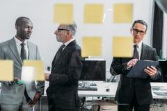 бизнесмен при блокнот смотря липкие примечания пока многокультурные коллеги имея обсуждение Стоковые Фото