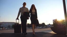 Бизнесмен при его женский коллега идя до конца входит в к чемодану стержня и крена на колесах Бизнесмен и сток-видео