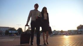 Бизнесмен при его женский коллега идя на чемодан улицы и крена города на колесах женщина бизнесмена акции видеоматериалы
