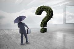 Бизнесмен при зонтик и портфель смотря вопросительный знак сделанный заводов Стоковая Фотография