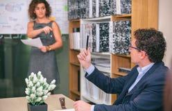 Бизнесмен при карандаш имея вопрос к женскому тренеру Стоковые Изображения