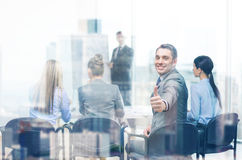 Бизнесмен при команда показывая большие пальцы руки вверх в офисе Стоковое Изображение RF
