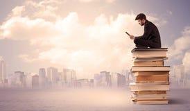 Бизнесмен при компьтер-книжка сидя на книгах Стоковые Изображения RF