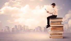 Бизнесмен при компьтер-книжка сидя на книгах Стоковая Фотография