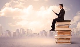 Бизнесмен при компьтер-книжка сидя на книгах Стоковое Фото